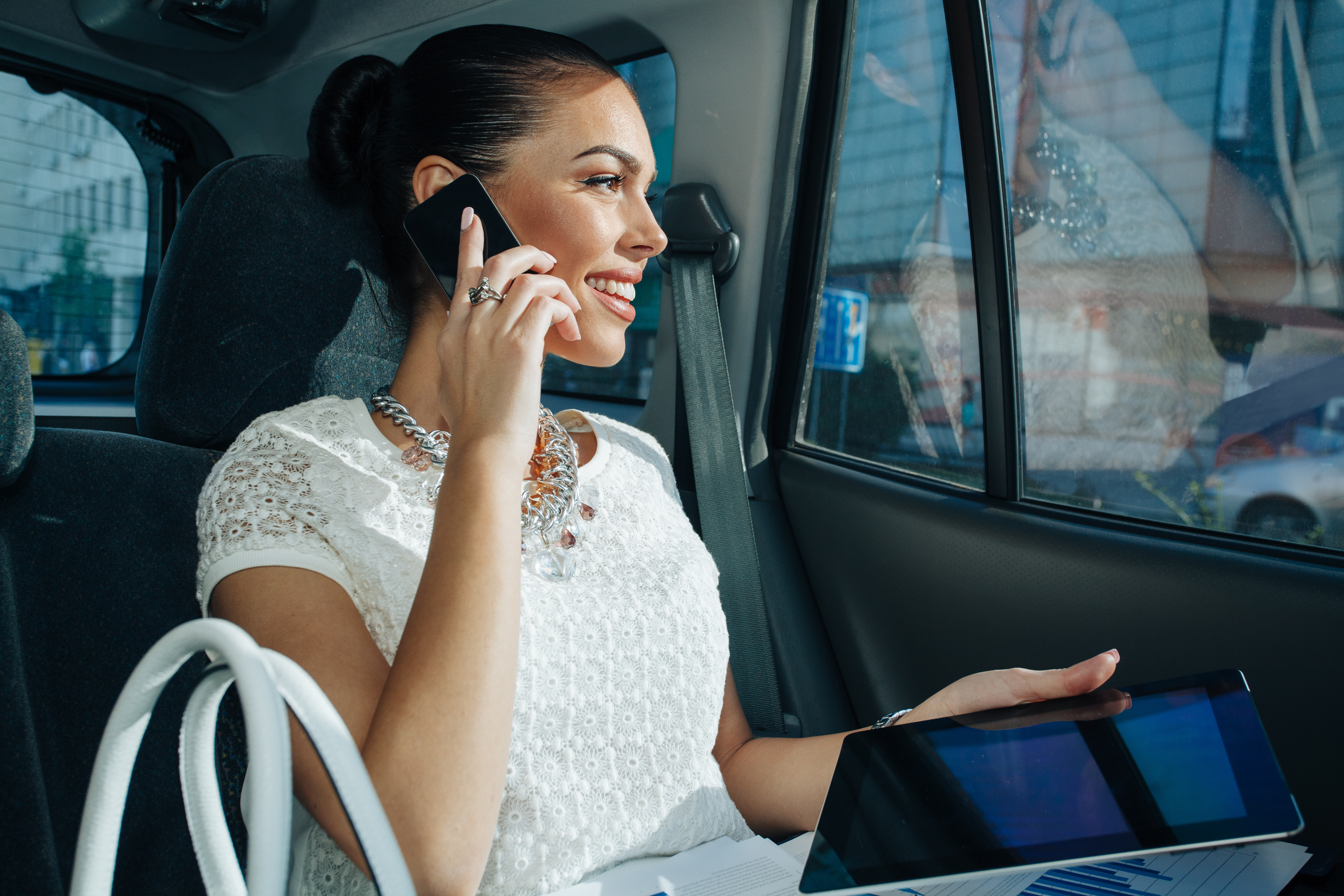 Young businesswoman talking on the phone in the back seat of car