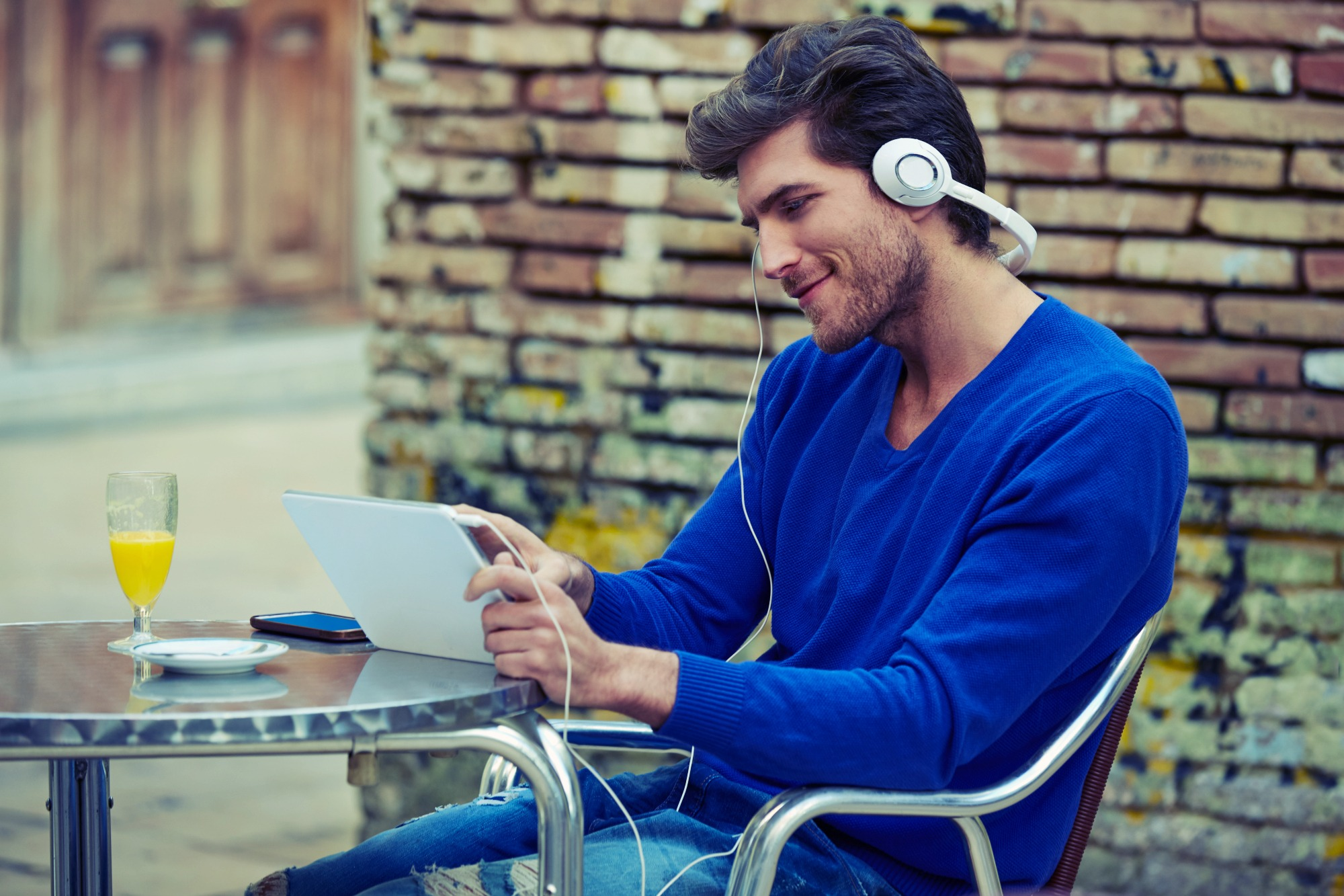 Young man with tablet pc touch listening music outdoor sitting with orange juice